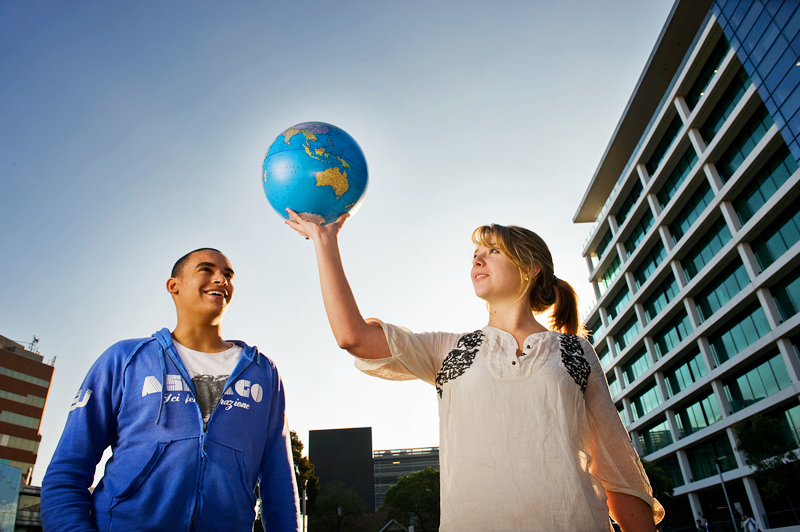 Students holding aloft a globe at Caulfield campus